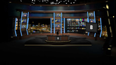 Virtual Set Studio 159 for vMix is a major network new desk set with monitors spaced around the room.